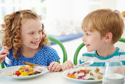 Two Children Eating Meal At Home Together