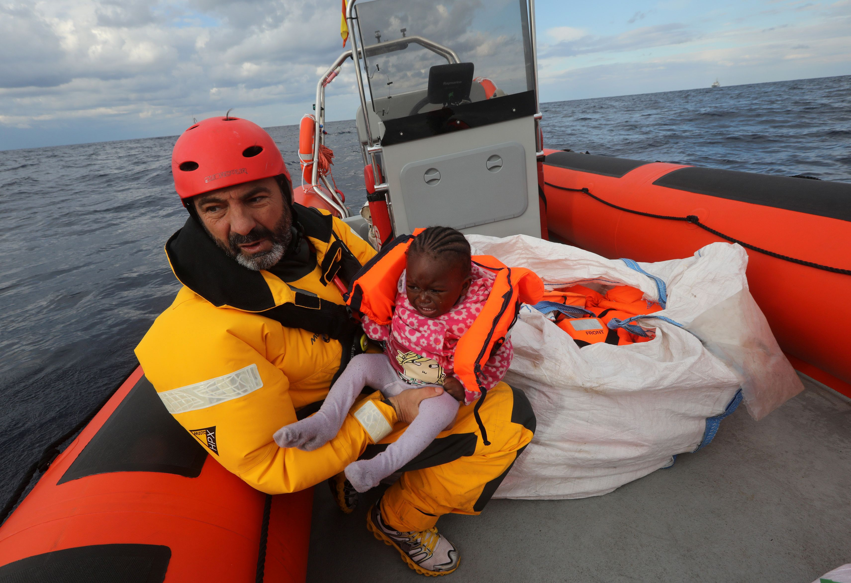 Oscar Camps, founder of Spanish NGO Proactiva Open Arms, holds a migrant child inside a rescue craft after pulling it from an overcrowded raft